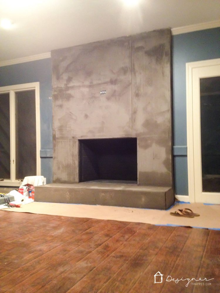 You can create a contemporary fireplace with concrete for less than $100. This full DIY concrete fireplace tutorial will show you exactly how!