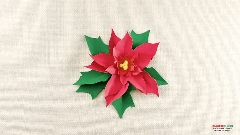 This DIY paper Poinsettia makes a perfect Christmas gift embellishment! Grab the free cut file and pattern to make your own.